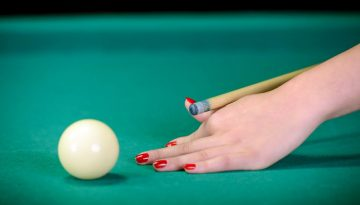 Billiard balls on green table and white ball on foreground.